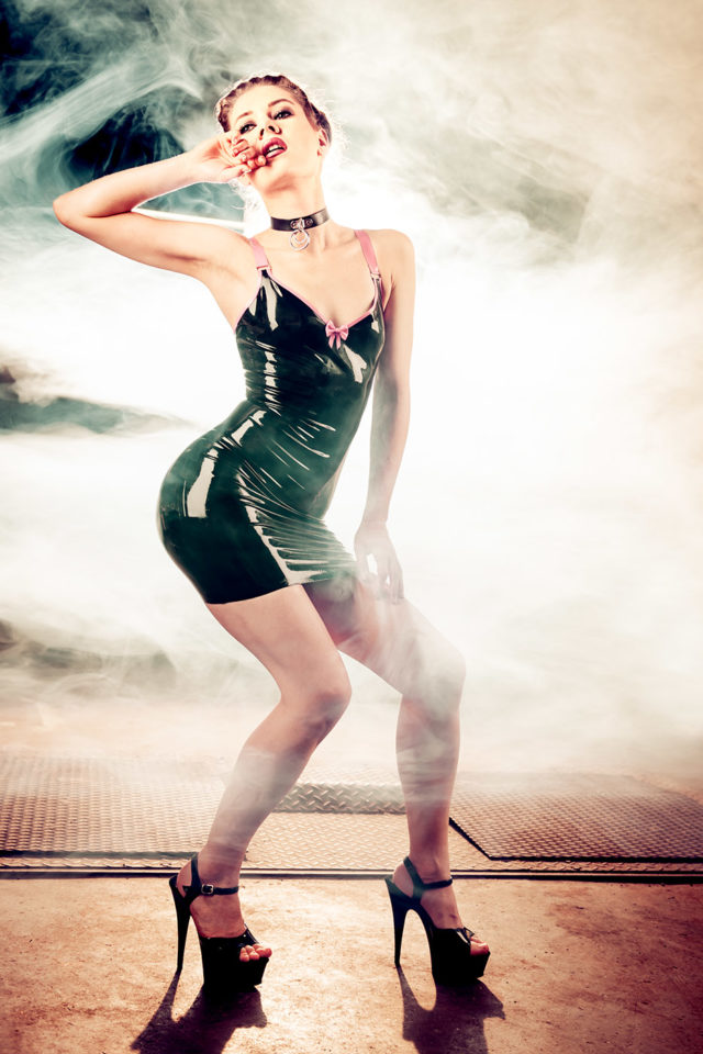A young woman in Latex Dress and curly hair surrounded by fog.